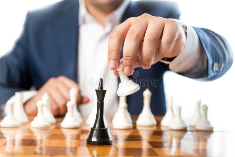 Close up do homem de negócios que joga a xadrez e que bate o rei preto foto de stock royalty free