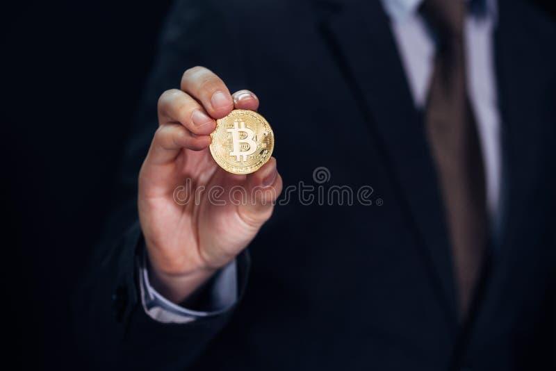 Close-up do homem de negócios que mostra e que guarda o sinal da moeda - indicando do bitcoin a moeda cripto e o futuro do banco  imagens de stock royalty free