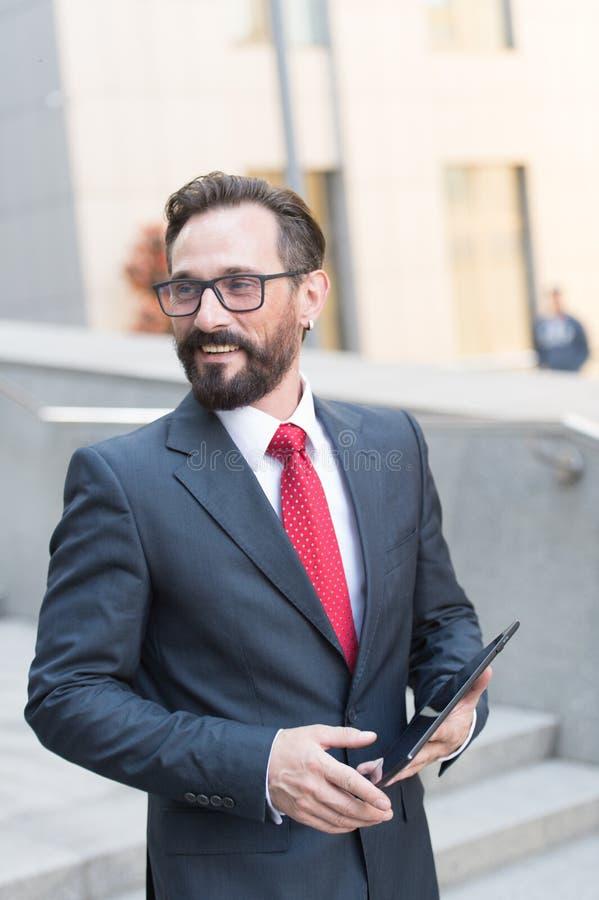 Close-up do homem de negócios que usa a tabuleta digital no trabalho Retrato do homem de negócios farpado considerável exterior imagem de stock