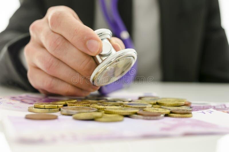 Homem de negócios que verifica o euro- dinheiro com o estetoscópio foto de stock