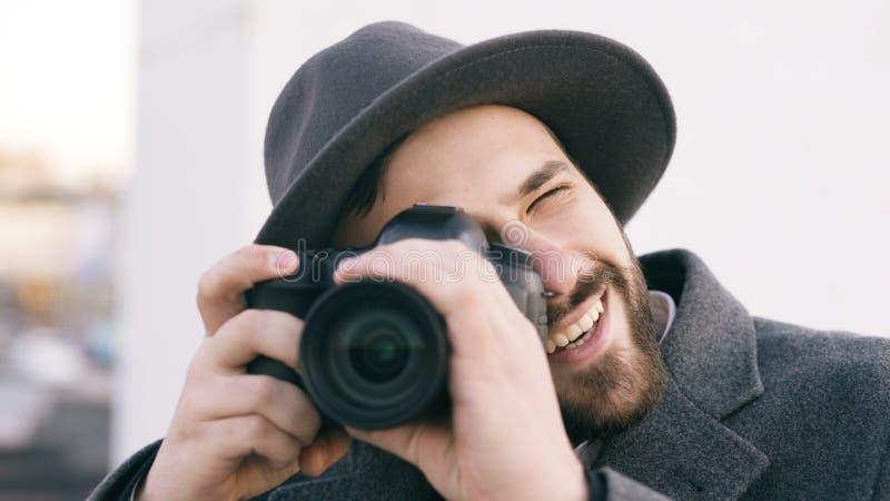 Close up do homem feliz dos paparazzi no chapéu que fotografa celebridades na câmera e que sorri fora imagens de stock royalty free