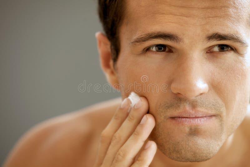 Close-up do homem novo que aplica o creme de rapagem fotografia de stock