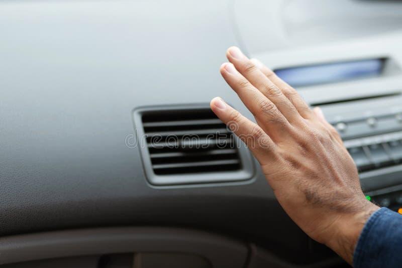 Close up do homem do punho que verifica ajustando o ar de condicionar o sistema de refrigeração com o fluxo do ar frio no carro fotografia de stock