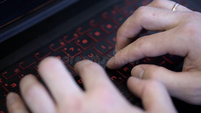 Close-up do homem que datilografa no teclado preto com luminoso grampo As mãos dos homens que datilografam no teclado elegante mo imagens de stock royalty free