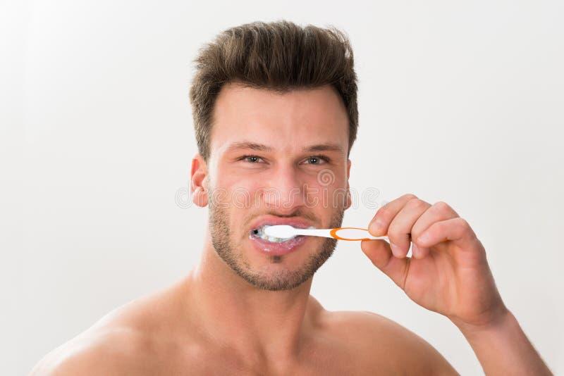 Close-up do homem que escova seus dentes foto de stock