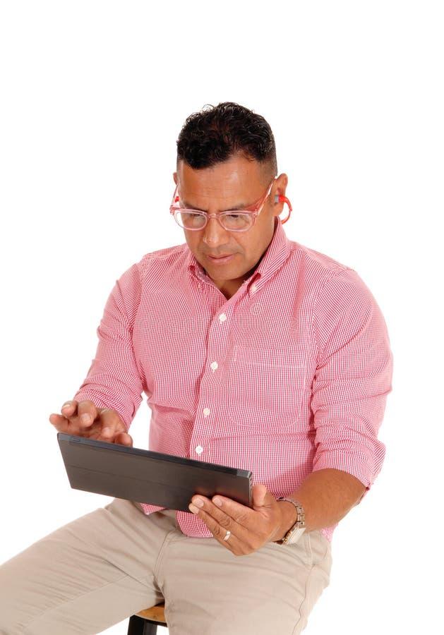 Close up do homem que trabalha no PC da tabuleta fotografia de stock