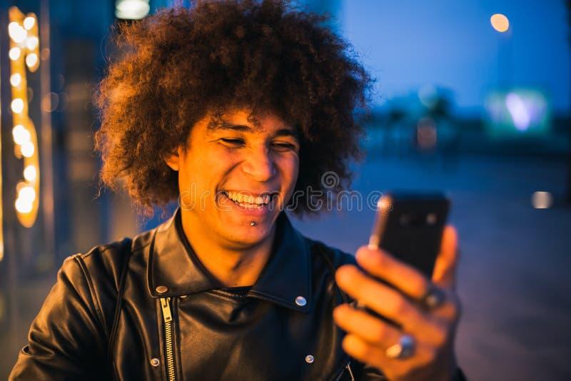 Close up do indivíduo afro-americano novo que usa o telefone esperto na rua na noite fotografia de stock royalty free