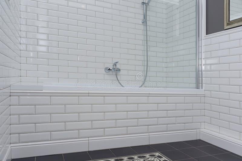 Close-up do interior do banheiro As paredes são cinza pintado, coberto com os azulejos decorativos com os tijolos lustrosos branc imagem de stock royalty free
