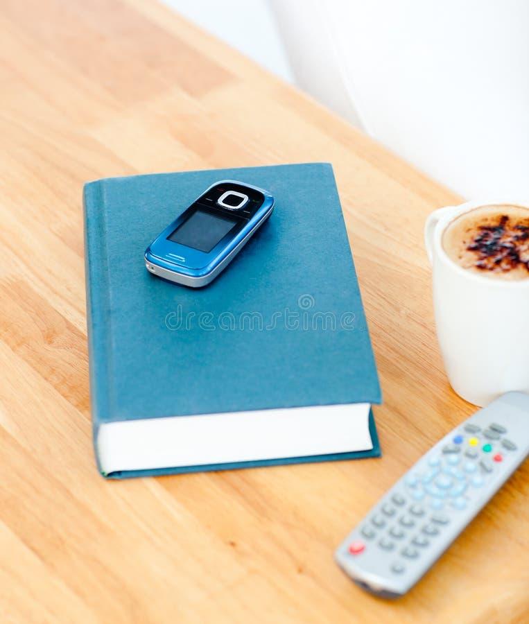Close-up do livro, telemóvel, telecontrole, chávena de café fotografia de stock royalty free