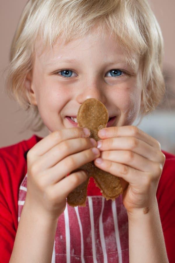Close-up do menino bonito que sustenta o homem de pão-de-espécie imagens de stock