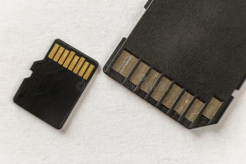 Close-up do micro cartão de memória do SD e do adaptador do SD isolados no fundo branco do espaço da cópia Conceito moderno da te foto de stock royalty free