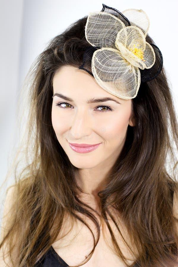 Close up do modelo fêmea de sorriso com a flor no cabelo foto de stock royalty free