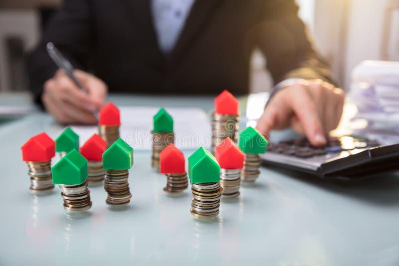 Close-up do modelo verde e vermelho On Stacked Coins da casa fotografia de stock royalty free
