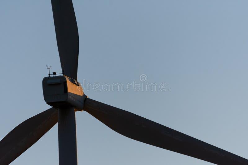 Close-up do moinho de vento em um por do sol com raios de sol alaranjados e o céu claro imagem de stock