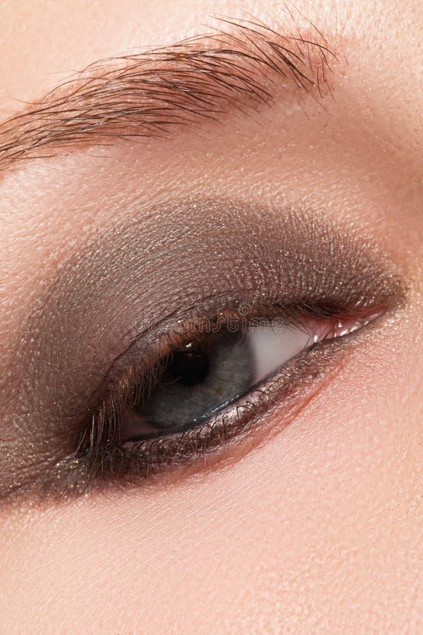 Close-up do olho azul da mulher com composição fumarento bonita Cosméticos & composição foto de stock