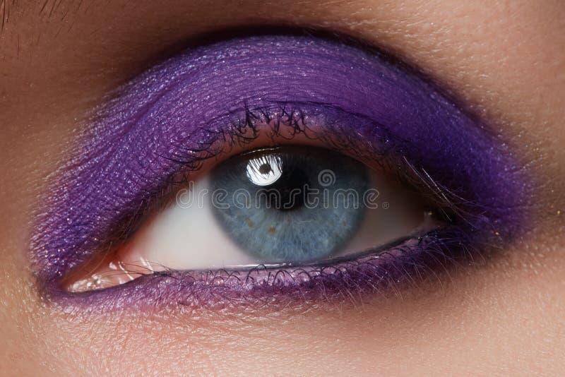 Close-up do olho azul da mulher com composição fumarento bonita Cosméticos & composição imagens de stock