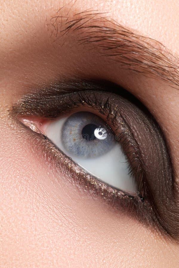 Close-up do olho azul da mulher com composição fumarento bonita Cosméticos & composição imagem de stock