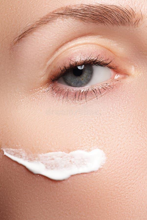 Close-up do olho bonito da mulher Mulher que aplica o creme hidratando fotografia de stock
