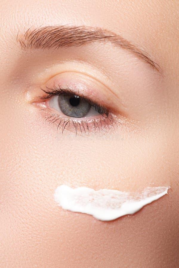 Close-up do olho bonito da mulher Mulher que aplica o creme hidratando fotografia de stock royalty free