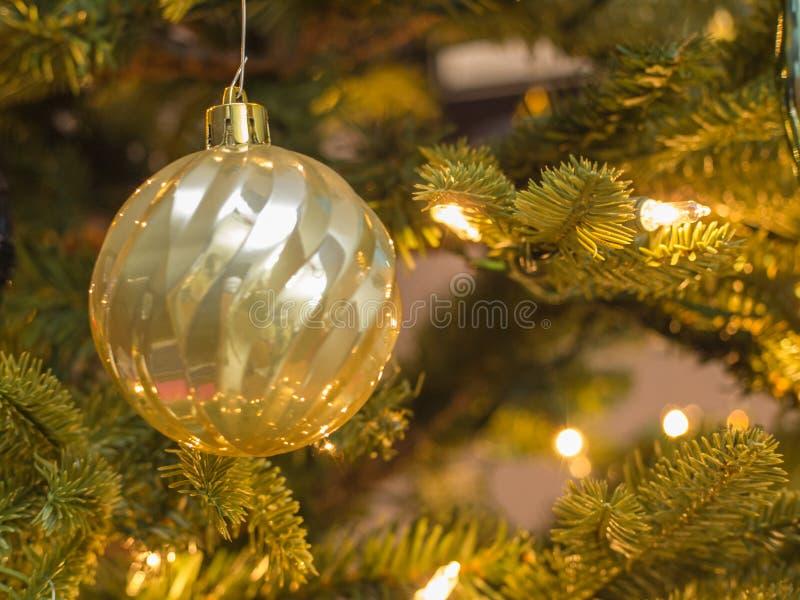 Close up do ornamento da bola do ouro com luzes douradas e fundo borrado imagens de stock royalty free