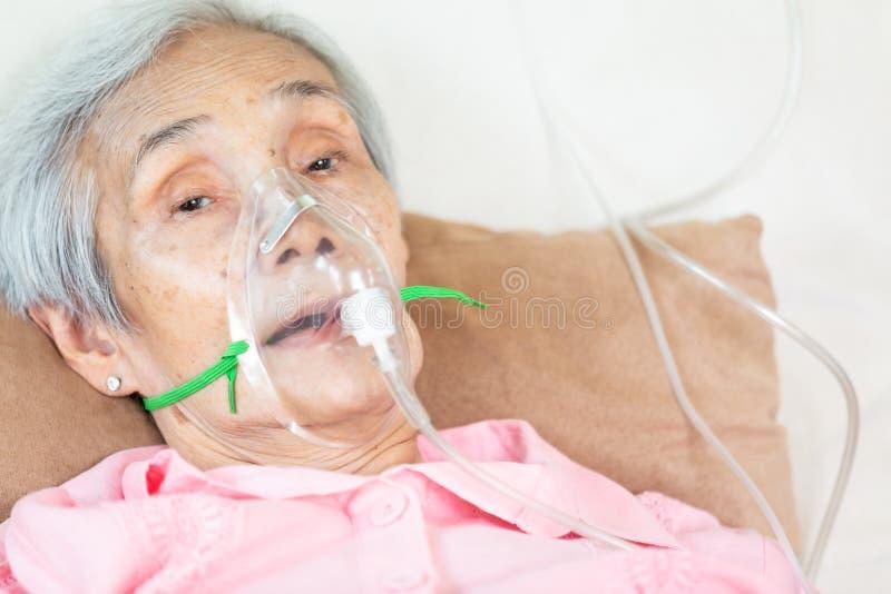 Close up do paciente superior fêmea que põe a inalação ou máscara de oxigênio na cama de hospital ou casa, mulher asiática idosa  fotografia de stock