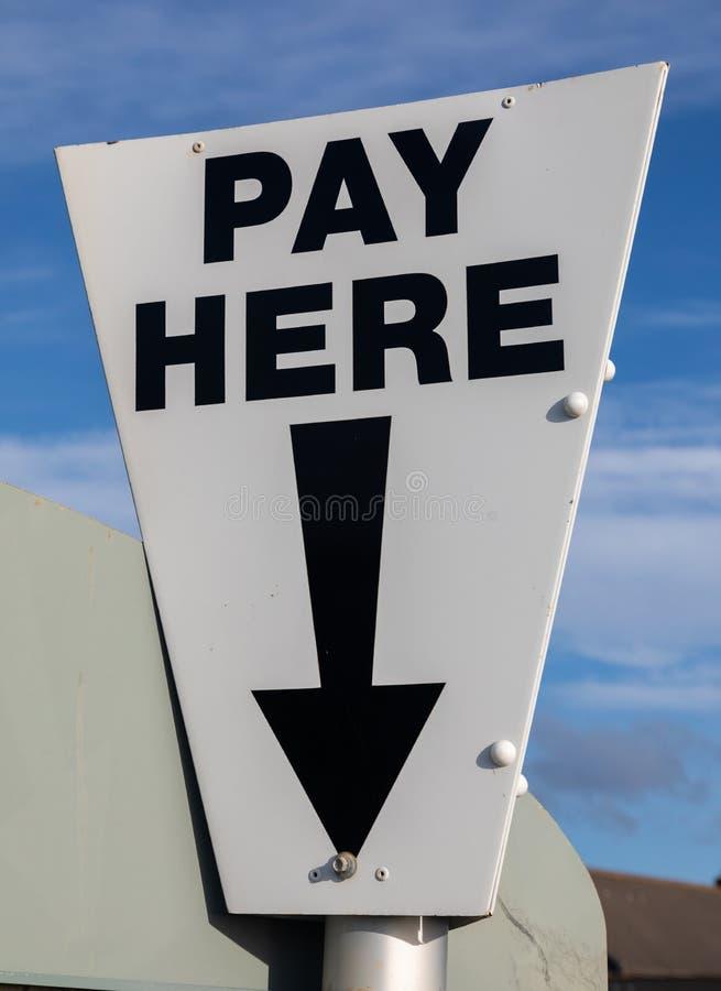 Close-up do pagamento de um sinal preto e branco triangular próximo aqui em um St Annes do parque do cark mar Fylde costa no feve imagem de stock