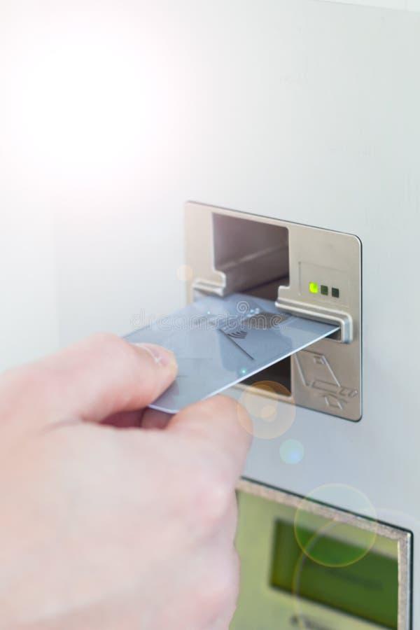 Close-up do person& x27; mão de s que introduz o cartão de crédito na máquina ao bilhete do pagamento foto de stock royalty free