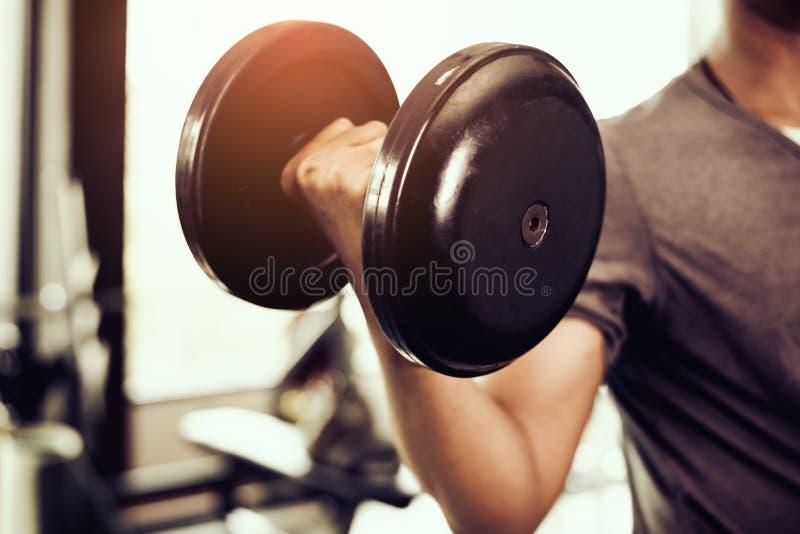 Close up do peso homem novo que levanta pesos pesados Equi do esporte imagem de stock royalty free