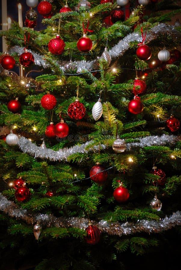 Close up do pinho três do Natal com vermelho e decorações do brilho da prata imagens de stock
