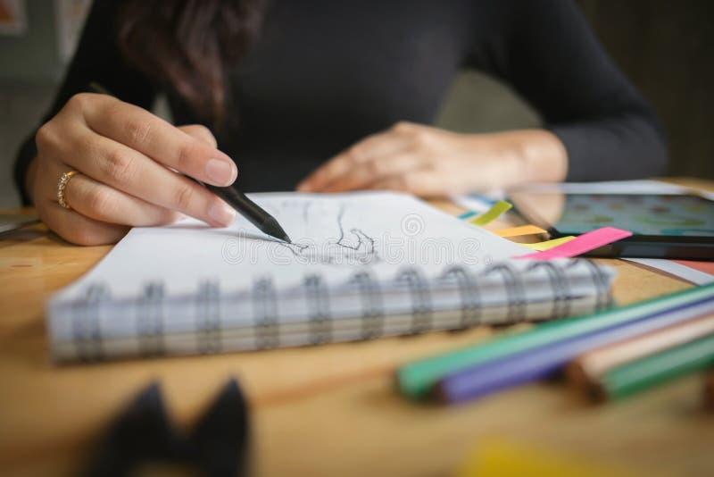 Close-up do projeto de funcionamento criativo novo do desenhador de moda em um escritório domiciliário moderno foto de stock royalty free