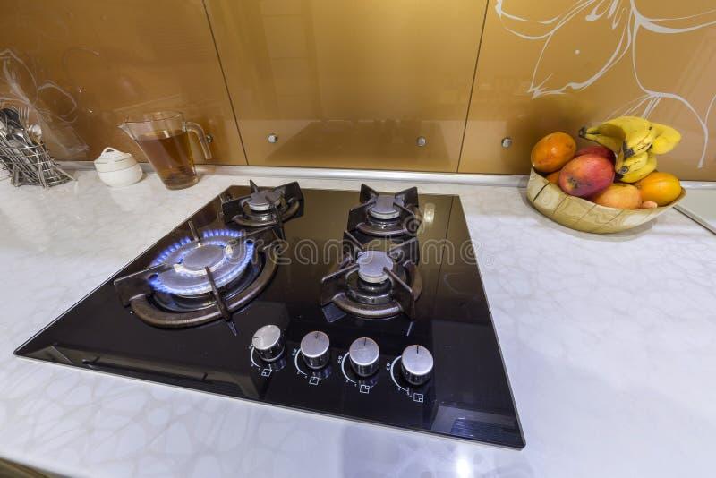 Close-up do queimador da chama do fogão de gás, bacia com fruto no contador de mármore Cozinha cabida moderna luxuosa com todos o foto de stock royalty free