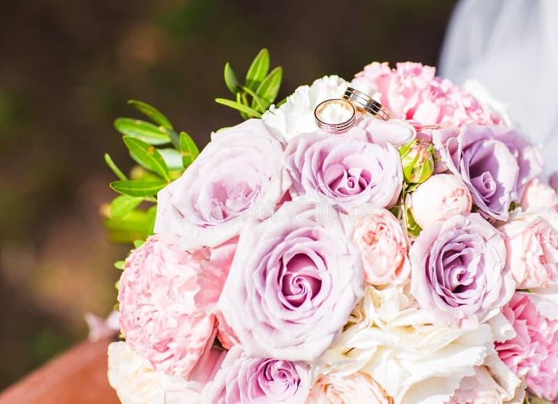 Close-up do ramalhete e das alianças de casamento da noiva fotos de stock royalty free