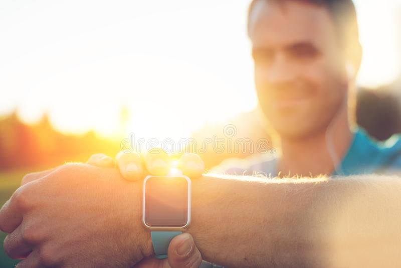 Close-up do relógio esperto no pulso e no atleta de sorriso no fundo imagens de stock royalty free