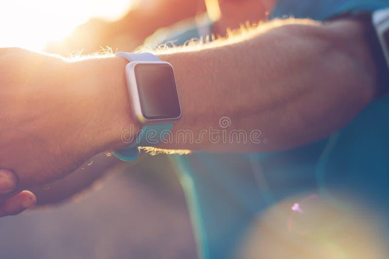 Close-up do relógio esperto no pulso do ` s do atleta quando ele que faz o aquecimento imagens de stock