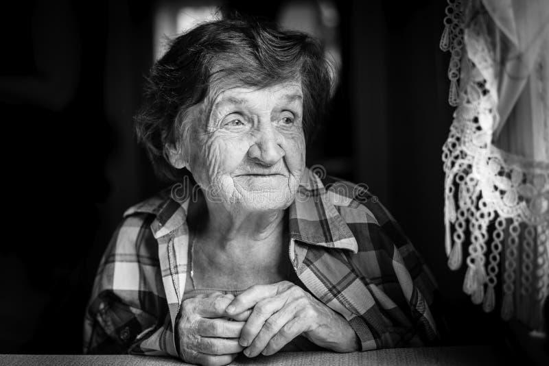 Close-up do retrato de uma mulher idosa, na casa pela janela, imagens de stock royalty free