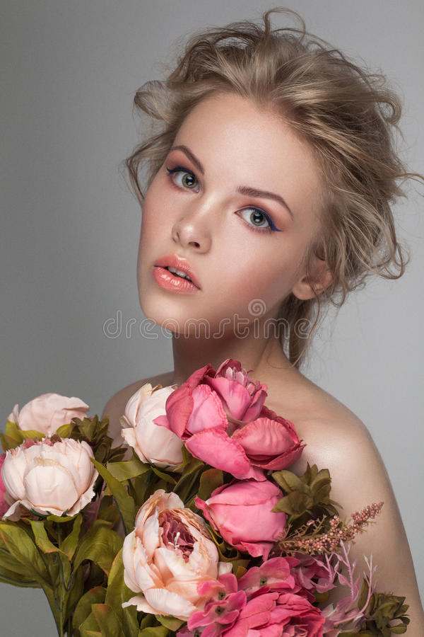 Close up do retrato de uma mulher loura bonita nova com flores frescas imagens de stock royalty free