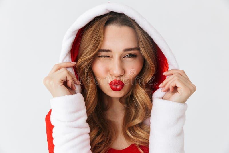 Close up do retrato do vestido vermelho vestindo flertando do Natal da mulher 20s que sorri e que está, isolado sobre o fundo bra fotografia de stock