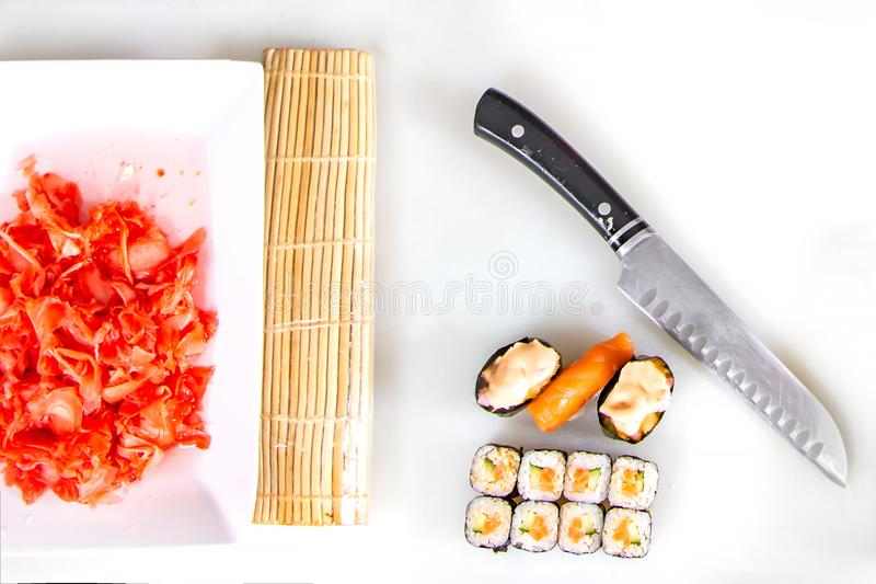 Close up do rolamento acima do sushi na cozinha com faca e ingredientes imagens de stock royalty free