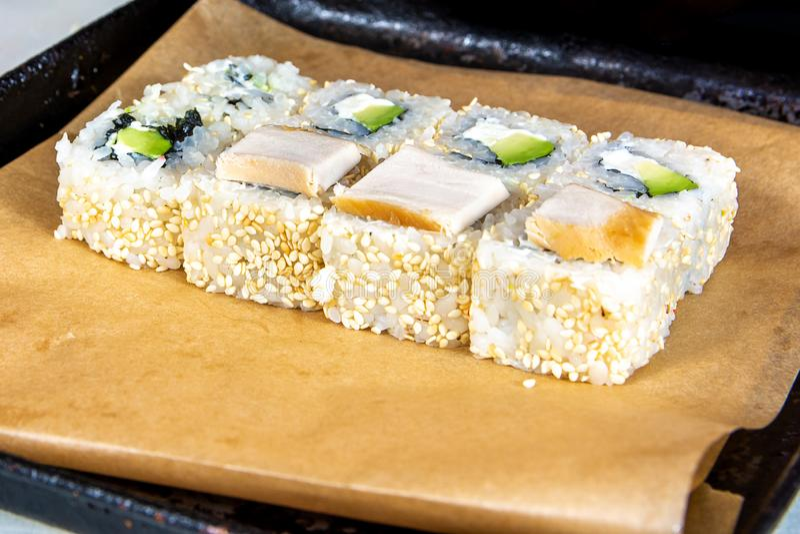 Close up do rolamento acima do sushi na cozinha com faca e ingredientes foto de stock