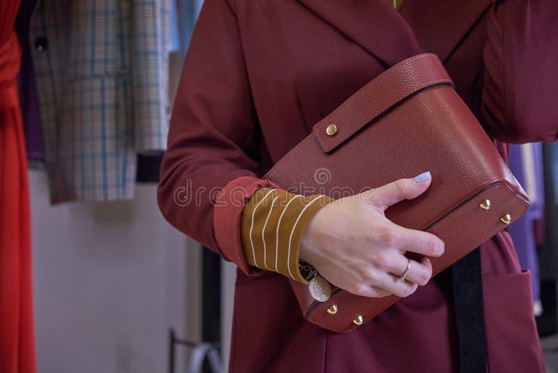Close up do saco pequeno vermelho à disposição da mulher Revestimento vermelho do equipamento da forma da mola da queda e calças  imagem de stock royalty free