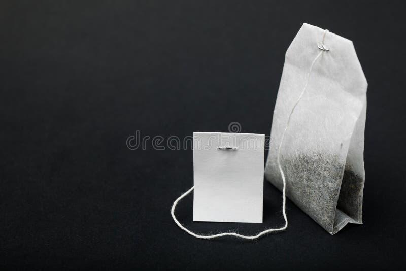 Close-up do saquinho de chá branco isolado no fundo preto, modelo imagem de stock royalty free