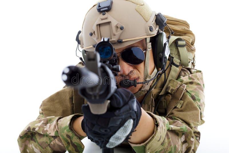 Close up do soldado que encontra-se no assoalho com o rifle sobre o branco fotos de stock royalty free