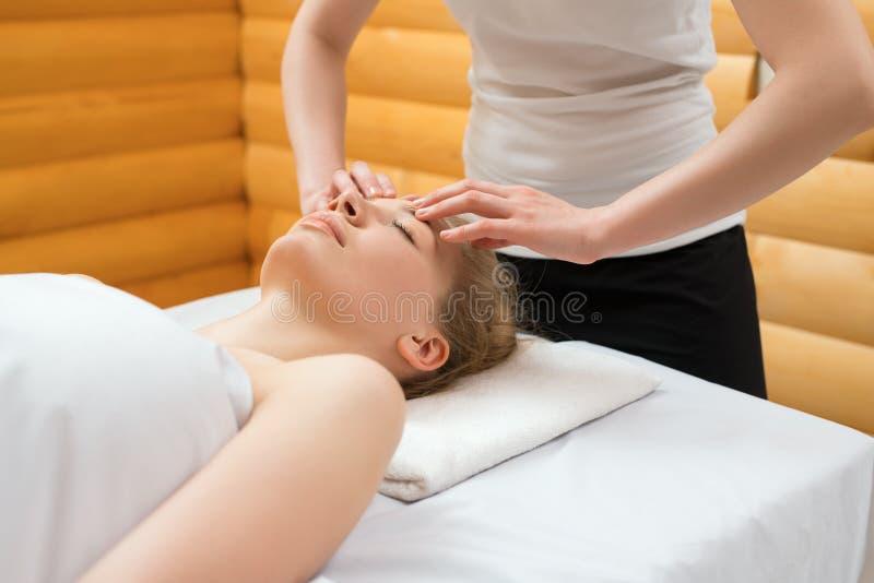Close-up do terapeuta que faz a massagem de cara em termas fotos de stock royalty free