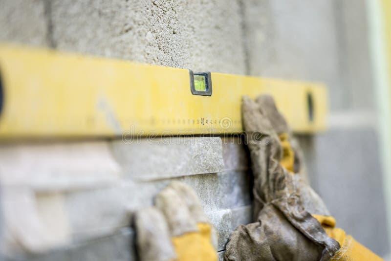 Close up do trabalhador manual que veste as luvas protetoras que guardam um yel imagem de stock