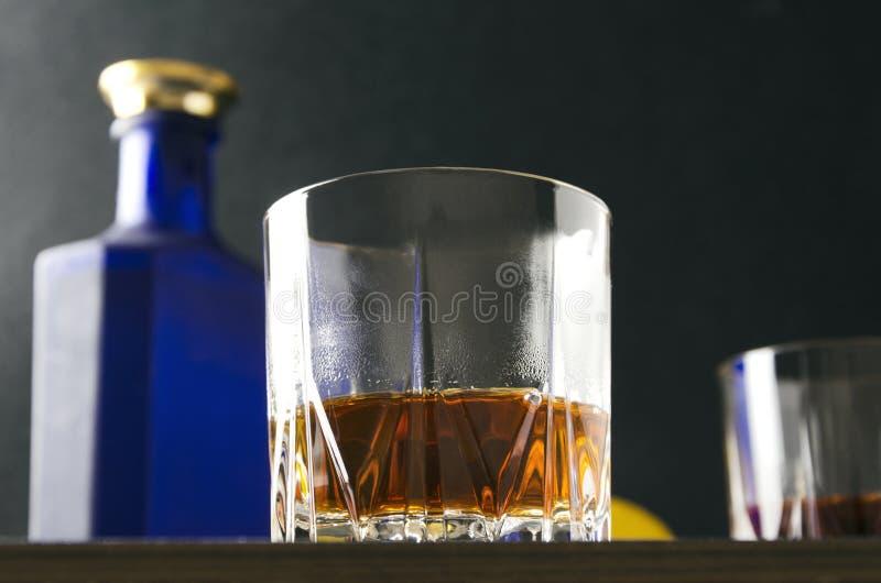 Close up do vidro da aguardente contra a garrafa e do outro de vidro, limão Foto do baixo ângulo imagens de stock royalty free