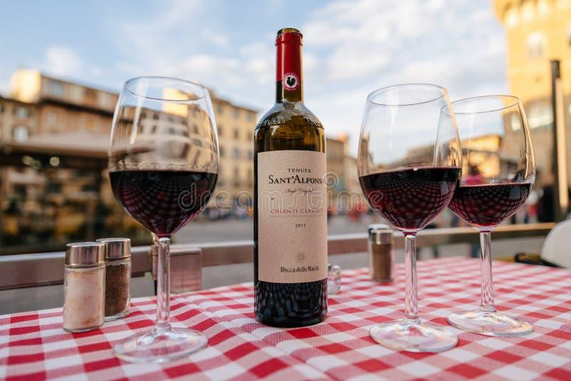 Close up do vinho tinto Sant Alfonso Chianti Classico da garrafa e dos vidros na tabela fotos de stock
