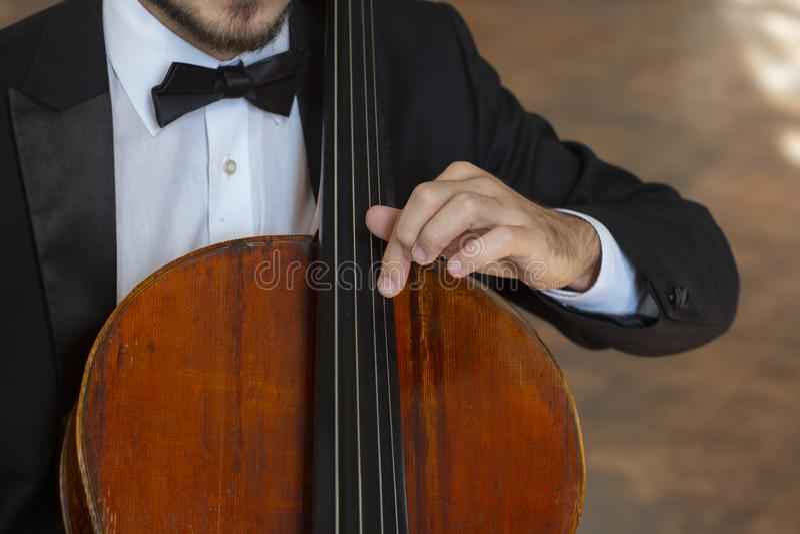 Close-up do violoncelo com mão de uma criança que guarda a curva imagem de stock