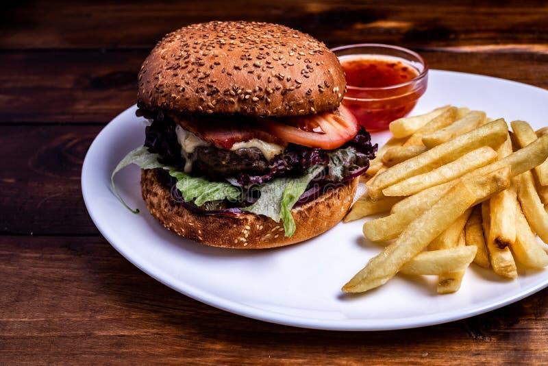 Close up dobro fresco do hamburguer na tabela rústica de madeira com as fritadas rústicas da batata A casa fez o Hamburger com ca fotos de stock royalty free