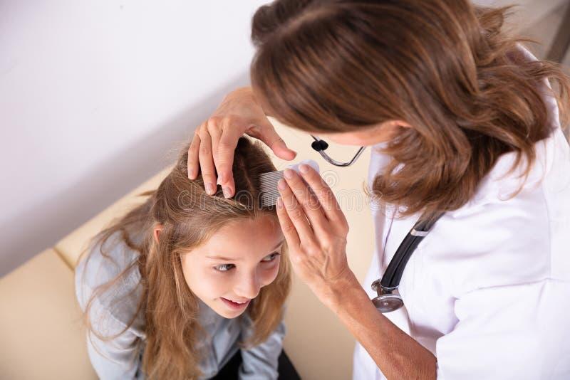 Doctor Examining Girl`s Hair stock photo