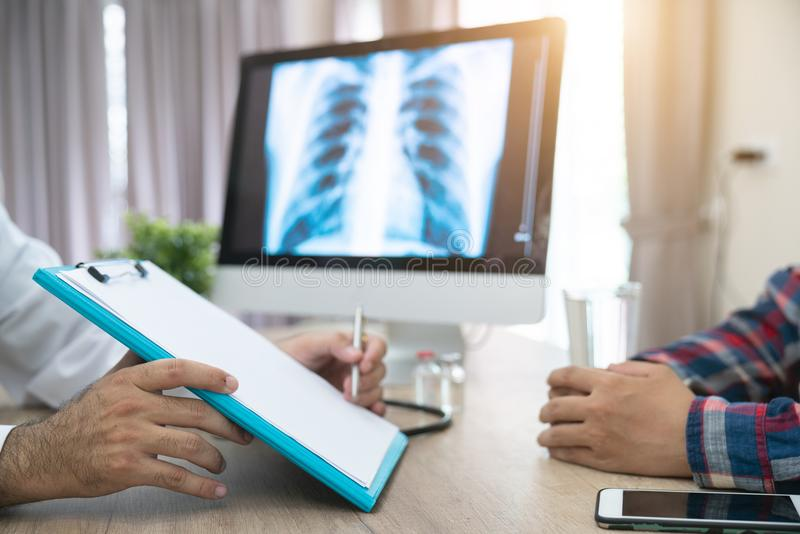 Close up of doctor filling up an application form while consulting patient stock photography